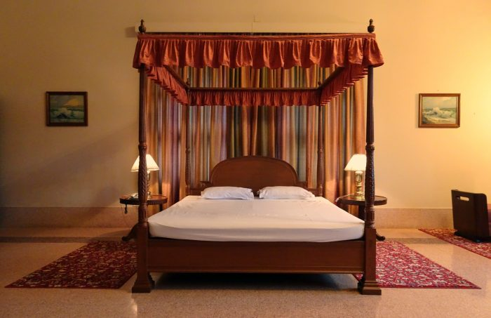 wooden frame canopy bed with curtains